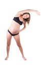 Smiley pregnant woman doing stretching exercise Royalty Free Stock Photo