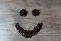 Smiley shaped figure made out of coffee beans on top of a table Royalty Free Stock Photo
