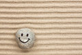 Smiley stone lying on the sand Royalty Free Stock Photo
