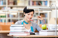 Smiley woman reads sitting at the desk with green apple surrounded with piles of books library academic achievement Royalty Free Stock Photo