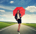 Smiley woman with red umbrella standing on the road over green field and blue sky Stock Photos