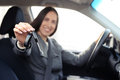 Smiley woman sitting in car and showing the car key focus on Stock Images