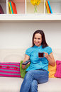 Smiley woman watching tv holding cup tea Royalty Free Stock Photos