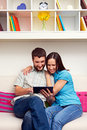 Smiley young couple looking tablet pc Royalty Free Stock Image