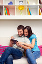 Smiley young couple sitting sofa looking tablet pc Royalty Free Stock Image