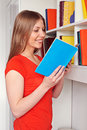 Smiley young woman reading novel Royalty Free Stock Photos