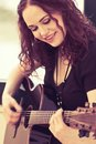 Smiling acoustic guitar player photo of a woman playing an by a window heavily filtered Stock Photos