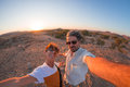 Smiling adult couple taking selfie in the Namib desert, Namib Naukluft National Park, main travel destination in Namibia, Africa. Royalty Free Stock Photo