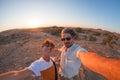 Smiling adult couple taking selfie in the Namib desert, Namib Naukluft National Park, main travel destination in Namibia, Africa.