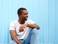Smiling african american man sitting against blue background Royalty Free Stock Photo