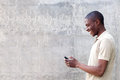 Smiling african american man walking and looking at cellphone Royalty Free Stock Photo