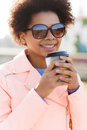 Smiling african american woman drinking coffee drinks and people concept young or teenage girl from paper cup outdoors Stock Photo