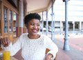 Smiling african american woman sitting at outdoor restaurant Royalty Free Stock Photo