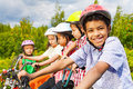 Smiling african guy in helmet with friends behind his sitting on bikes Royalty Free Stock Photos