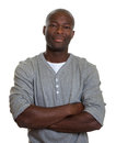 Smiling african man in a grey shirt with crossed arms at camera on an isolated white background Royalty Free Stock Images
