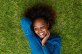 Smiling african woman lying on grass portrait from above of a Royalty Free Stock Images