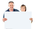 Smiling aged couple displaying blank banner Royalty Free Stock Images