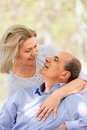 Smiling aged man and woman hugging each other men women in summer park Stock Photography