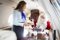 Smiling airhostess serving cookies to santa in mid adult private jet Stock Photo