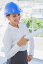 Smiling architect holding plans and wearing hardhat blue in a modern office Royalty Free Stock Image