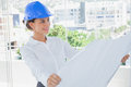 Smiling architect rolling out a blueprint and wearing hardhat in modern office Royalty Free Stock Images