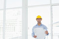 Smiling architect in yellow hard hat with blueprint in office portrait of a young a bright Stock Photo