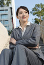 Smiling asian business woman sit on stair of outside in modern city Stock Images