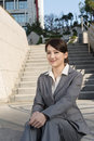 Smiling asian business woman sit on stair of outside in modern city Stock Image