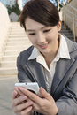 Smiling asian business woman using cellphone and sit on stairs a at outside in modern city Royalty Free Stock Photo