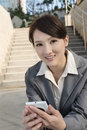 Smiling asian business woman using cellphone and sit on stairs a at outside in modern city Royalty Free Stock Images