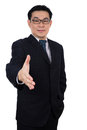 Smiling Asian Chinese man wearing suit posing with handshake ges Royalty Free Stock Photo