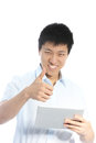 Smiling asian man giving thumbs up success approval one hand holding tablet other isolated white Stock Image