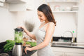 Smiling asian woman making smoothie with fresh vegetables in the Royalty Free Stock Photo