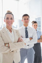 Smiling attractive businesswoman standing with arms folded in front of colleagues Stock Image