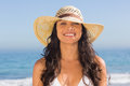 Smiling attractive dark haired woman wearing straw hat posing on the beach Royalty Free Stock Image