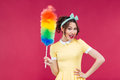 Smiling attractive pinup girl holding colorful duster brush