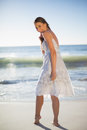 Smiling attractive woman looking over shoulder at camera on the beach Royalty Free Stock Images