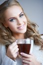 Smiling attractive woman with a mug of coffee lovely long curly blond hair enjoying as she looks at the camera friendly Royalty Free Stock Photo