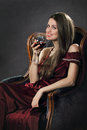 Smiling attractive woman poses with a glass of red wine elegant silky dress Royalty Free Stock Photos