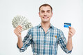 Smiling attractive young man holding cash and credit card Royalty Free Stock Photo