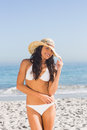 Smiling attractive young woman wearing straw hat posing on the beach Stock Photography