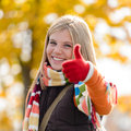 Smiling autumn teenager girl thumbs up forest blonde fall Stock Images