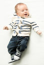 Smiling baby boy in jeans and sweater lying on bed Royalty Free Stock Photo