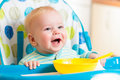 Smiling baby eating food on kitchen boy Stock Image