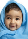 Smiling Baby Girl Draped in Blue Blanket Royalty Free Stock Photography