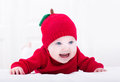 Smiling baby girl on her tummy wearing red apple hat Royalty Free Stock Photo