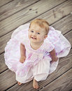 Smiling baby girl in a pink dress on wood background one year old Royalty Free Stock Photo
