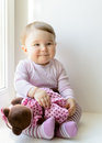 Smiling baby girl plays with toy bear Royalty Free Stock Photo