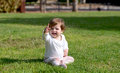 Smiling baby girl sitting on a grass Royalty Free Stock Photo