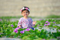 Smiling baby girl wearing colorful suit and flower hat is playin Royalty Free Stock Photo